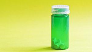 green pill bottle on yellow