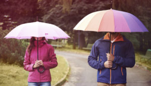 man and woman hold umbrellas
