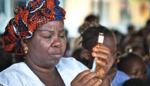 woman prepares measles vaccine in Guinea