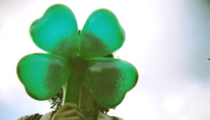 woman holds plastic shamrock in front of face