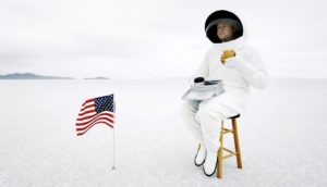 astronaut eats lunch on stool sadly