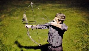 man shoots bow and arrow