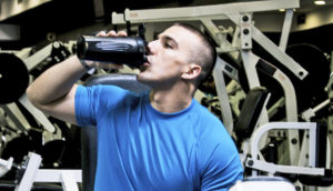 man at gym drinks supplement
