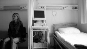 woman sits in empty hospital room