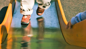 kid runs up the slide