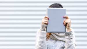 woman holds tablet in front of face