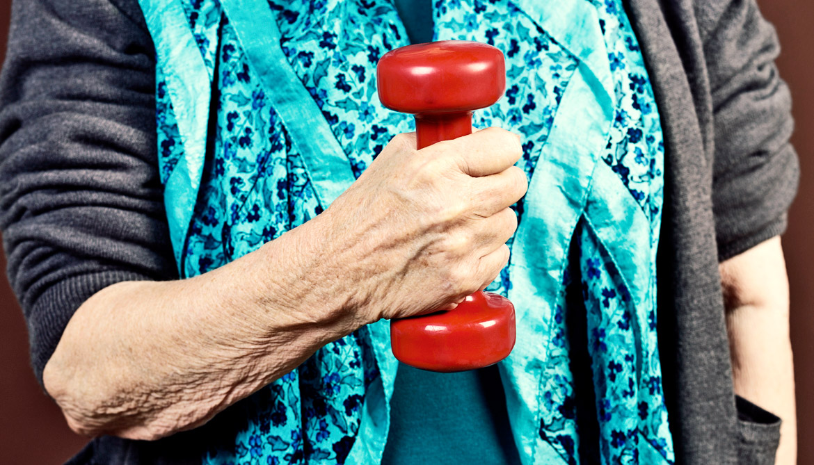 elderly woman holds red weight