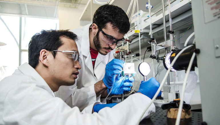 Chengxiang Xiang (left) and Erik Verlage assemble the water-splitting device.