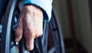 elderly person's hand on wheelchair