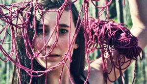 woman's face behind yarn tangle