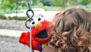 girl holds elmo doll on swing