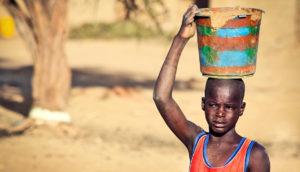 boy carries bucket in Senegal