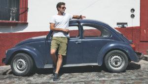 man standing beside a VW bug