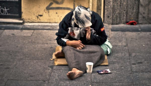 homeless woman sits on street