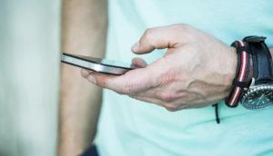 man's hand texting