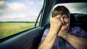 older woman in car holds up fist