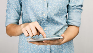 woman in blue shirt uses tablet