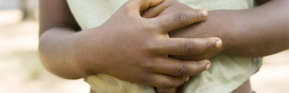 child hold hands over stomach