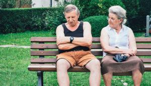 older man sleep on bench with wife