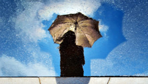silhouette with umbrella against blue sky