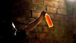 man holds wine bottle up to light