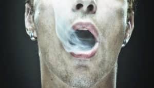 man blows smoke