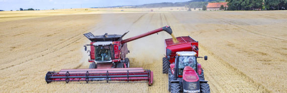 combine and tractor in a wheat field