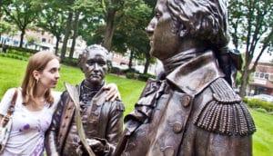 woman hugs a statue of Alexander Hamilton