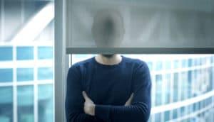 man's face hidden behind a window blind