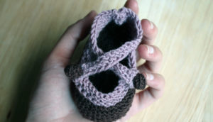 woman holds baby booties