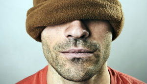 man wearing a brown cap over his eyes