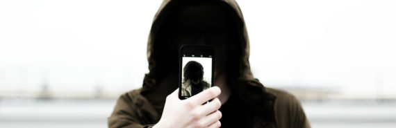 anonymous man holding an iphone