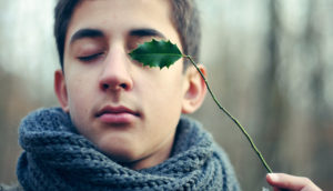young man holds a leaf over one eye