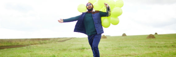 man running with balloons