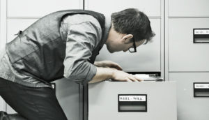 man looks in a filing cabinet