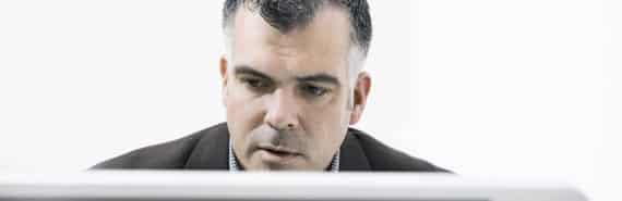 man stares at a computer monitor
