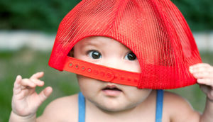 baby wears a red hat