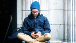 man in blue hat texting