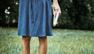 woman in blue skirt holds book