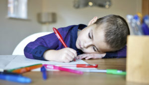 boy draws with red pen