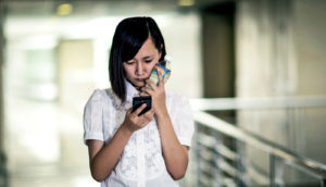 sad young woman looks at phone