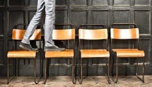 man walks on chairs