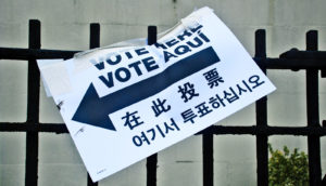 vote sign speared on fence