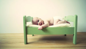 baby in a tiny green bed