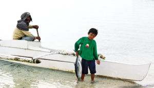 man and boy with boat and fish