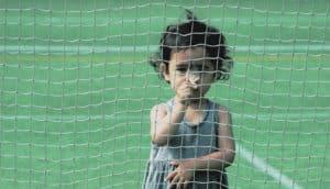 child hides behind a net