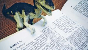 toy dinosaur and bible