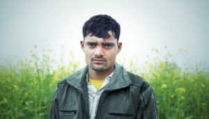 man stands near a field