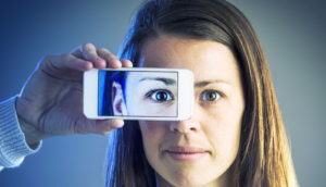 woman hold phone photo of eye over her eye