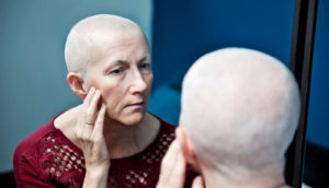 cancer patient looks in mirror
